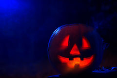 Blurry orange pumpkin with smoke and red fire inside. Royalty Free Stock Photo