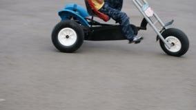 blurry Os pés são close-up As crianças montam uma bicicleta e no hoverboard no pavimento vídeos de arquivo