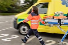 Blurry paramedics pulling gurney ambulance car. Blurry paramedics in hurry pulling gurney next to ambulance car royalty free stock photos