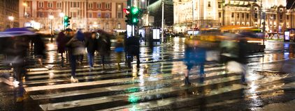 Blurry people crossing the city street in rainy night. Blurry people silhouettes crossing the city street in motion blur in rainy night Royalty Free Stock Image