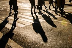 Blurry people and their shadows on crossing Royalty Free Stock Image