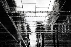 Blurry people reflection shadow on rainy city street Royalty Free Stock Photography