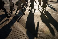 Blurry people and their shadows on crossing Stock Photos