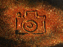 Blurry Photo Camera on golden and red glitter sparkle on black background Stock Images