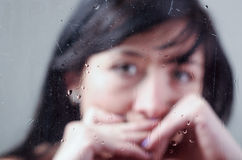 Blurry portrait of lonely girl behind wet glass Stock Photos