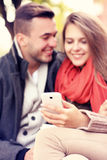 Blurry portrait of a young couple on a bench with smartphone in Stock Photo
