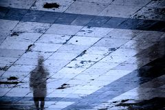 Blurry reflection shadow silhouette on a rainy sidewalk. Blurry reflection shadow of one person walking the city street patterned sidewalk on a rainy night stock photos