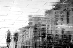 Blurry reflection silhouette of people walking wet city street royalty free stock photography