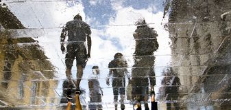Blurry reflection silhouettes of people walking on a rainy day royalty free stock images