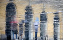 Blurry reflection  silhouettes of people walking on a rainy day. Blurry reflection shadow silhouettes of people walking on a rainy pedestrian street  in spring Stock Image