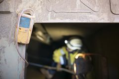 Blurry rope access miner working inside the confined space. While yellow gas test detector atmosphere is hanging on the entry door frame, construction mine site stock photo