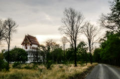 Blurry and scary landscape with buddhist temple, road and forest at sunset Stock Photo