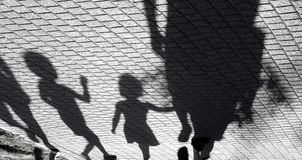 Blurry shadow of a little boy and a girl walking with adults royalty free stock photos