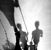 Blurry shadow silhouette of a senior person with walking stics. Blurry shadow silhouette of an elderly person walking with nordic poles sticks on sidewalk and Stock Photos