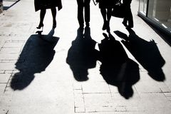 Blurry shadow silhouette of  people walking in high contrast. Blurry shadow silhouette of  people walking on city pedestrian street in high contrast black and stock photography