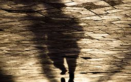 Blurry shadow silhouette of a person running on city street side. Blurry shadow silhouette of a person running on city patterned sidewalk in sepia tone Stock Image