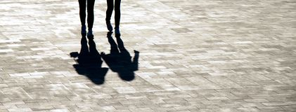 Blurry shadow silhouettes of two young women walking royalty free stock image