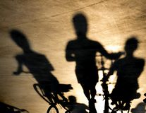Blurry shadow of three young women on bikes. Blurry shadow of three young women riding or pushing their bikes in sunset stock images