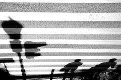 Blurry shadows of pedestrians waiting at crosswalk stock photo