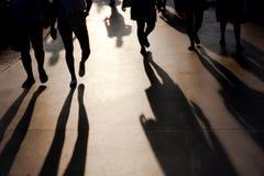 Blurry shadows of people walking on summer promenade. Blurry shadows of people walking towards the camera on seaside promenade in misty summer sunset Stock Photo