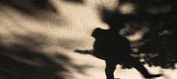 Blurry shadows of urban nature. Blurry shadows silhouette of a person and treetops in the park Stock Image