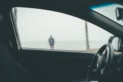 A blurry silhouette of a human seen through wet car window stock image