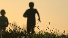 Blurry silhouette of kids running at sunset stock footage