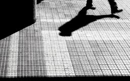 Silhouette and shadow of a person walking. Blurry silhouette of legs and shadow of a person walking  on a city sidewalk  in black and white high contrast Stock Photos