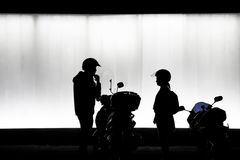 Blurry silhouette of man and woman standing next oto motorbike royalty free stock photos