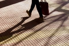 Blurry silhouette shadow of legs of a person carrying a bag while walking on tiled street sidewalk. Blurry silhouette shadow of legs of a person carrying a bag royalty free stock images
