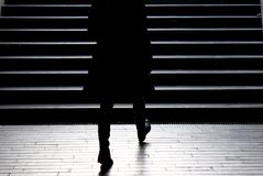 Blurry silhouette of young elegant woman climbing up the city st Royalty Free Stock Photo
