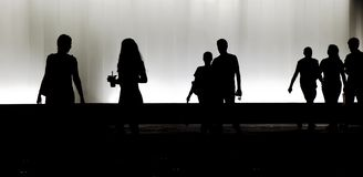 Blurry silhouette of young people walking in the black and white night stock photos
