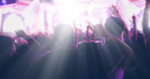 Blurry of silhouettes of concert crowd at Rear view of festival. Crowd raising their hands on bright stage lights Royalty Free Stock Photo