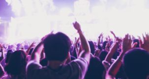 Blurry of silhouettes of concert crowd at Rear view of festival. Crowd raising their hands on bright stage lights Stock Photo
