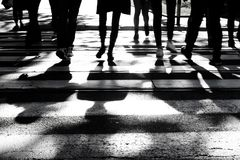 Blurry shadows and silhouettes of people on crossroad. Blurry silhouettes and shadows of people crossing the street on crosswalk in black and white, only legs stock image