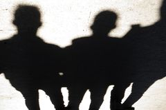 Blurry silhouettes and shadows of three people walking city street stock photos