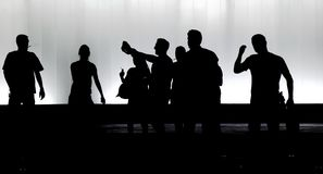 Blurry silhouettes of young people walking in the black and white night stock images