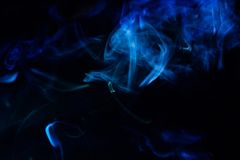 Blurry smoke abstract background blue color on black night . free form swirl flowing fog in the air royalty free stock photo