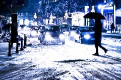 Blurry snowy city night traffic. With pedestrian silhouete crossing the street royalty free stock images