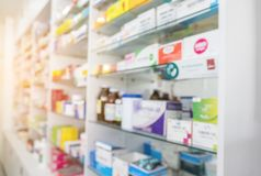 Blurry view of drug store and pharmacist. Blurred clean pharmacy with medicine on shelves. Defocus white drugstore