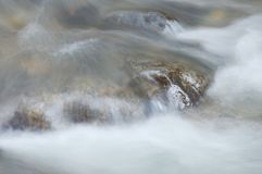 Blurry water flowing on the rock and wave splashing in river. Blurry water flowing on the rock and wave splashing in the river royalty free stock photography