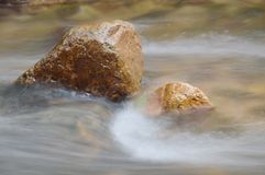 Blurry water flowing on the rock and wave splashing in river. Blurry water flowing on the rock and wave splashing in the river royalty free stock image