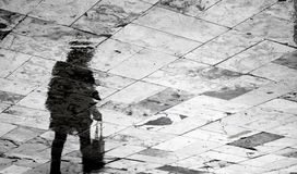 Blurry woman silhouette reflection on rainy patterned sidewalk Stock Photography