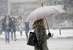 Blurry young women walking under umbrella in heavy snowfall royalty free stock images