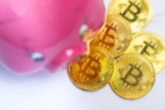 Blury background of Pig bank and a drop gold bitcoins on the white wooden background. Pig bank and a drop gold bitcoins on the white wooden background, a saving vector illustration