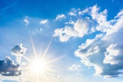 Blus niebo z chmurami i jaskrawym słońcem zdjęcia stock