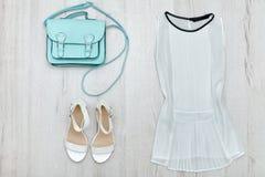 Blusa bianca, scarpe bianche e borsa concetto alla moda Priorità bassa di legno Immagine Stock