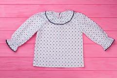 Blusa blanca en la tabla rosada Imagen de archivo