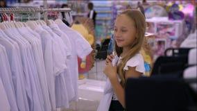 Blusa blanca que intenta y que cabe de la muchacha sonriente adorable en boutique metrajes
