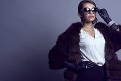 Blusa de seda blanca que lleva del modelo atractivo hermoso, capa de sable, guantes de cuero, gafas de sol y sistema de joyería l Imágenes de archivo libres de regalías